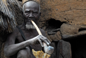 Taneka tribal man with a long pipe